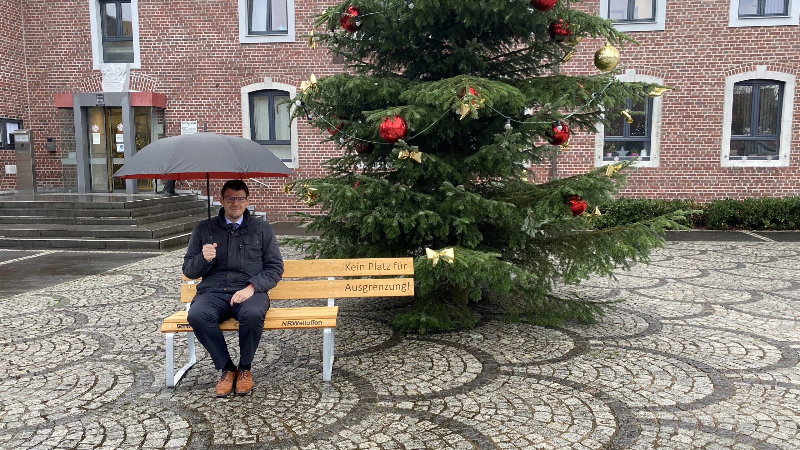 Das Foto zeigt Bürgermeister Michael Stock auf dem Rathausplatz nach der Übergabe der Bank durch die Lebenshilfe